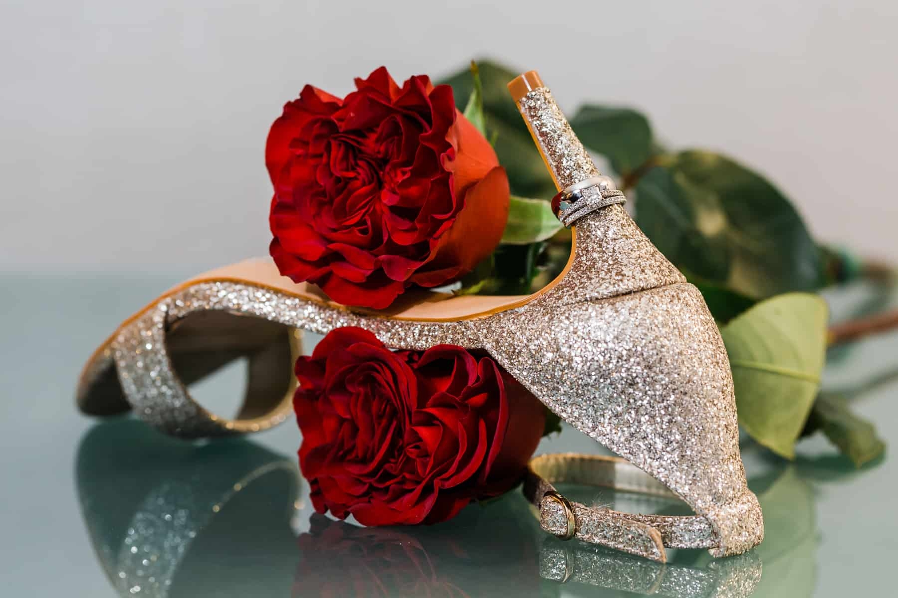Wedding shoe, rings, and red roses