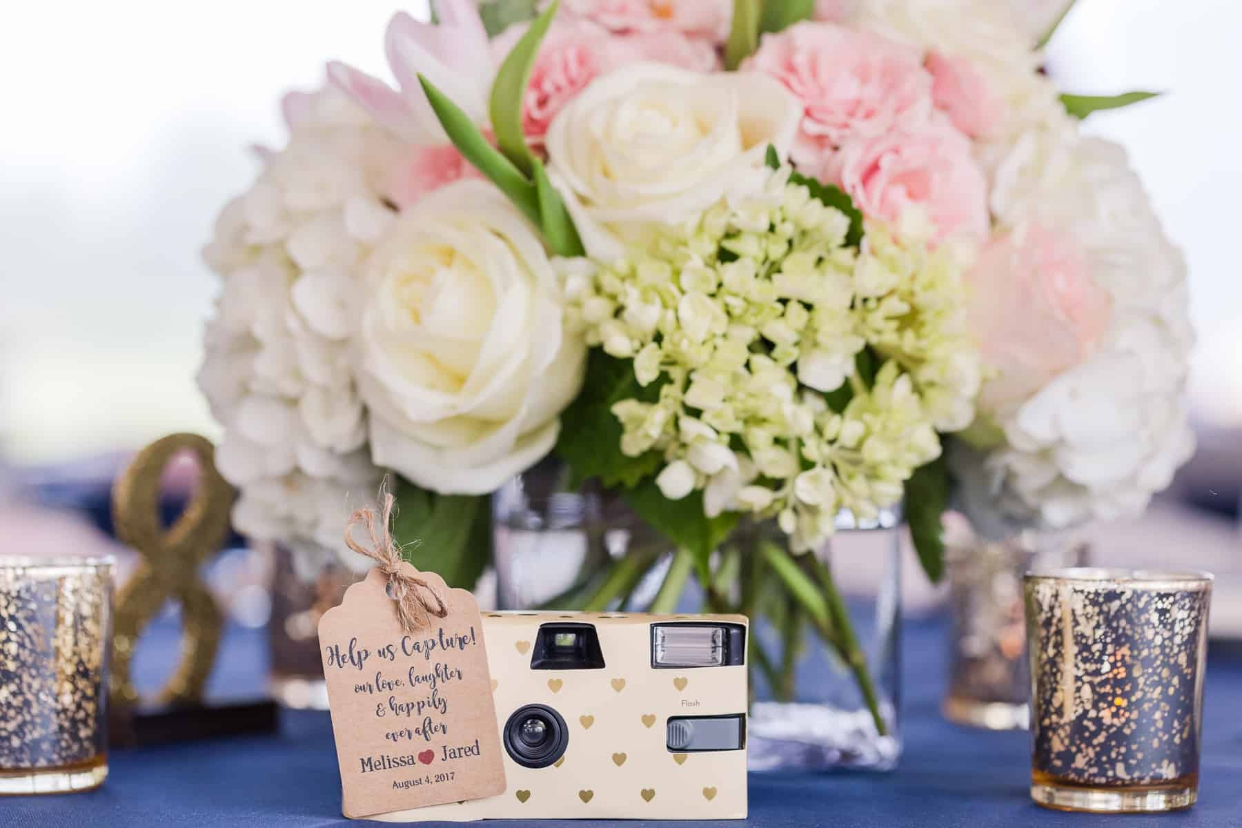 Wedding table bouquet and camera for guests